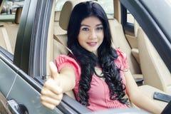 La belle femme à l'intérieur des salons automobiles APPROUVENT le signe Images libres de droits