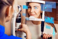 La belle femme à la réception à l'ophtalmologue vérifie son v images stock