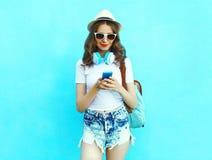La belle femme écoute la musique et smartphone d'utilisation au-dessus de bleu coloré Photo stock