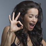 La belle femme affiche un ok de signe Images stock