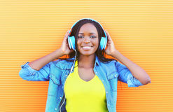 La belle femme africaine de sourire avec apprécier d'écouteurs écoute la musique Photographie stock