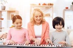 La belle femme agée enseigne de petits petits-enfants à jouer le synthétiseur Images stock