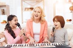 La belle femme agée joue sur le clavier avec les petits-enfants qui chantent dans le microphone images libres de droits
