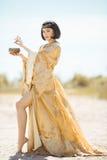 La belle femme aiment la Reine égyptienne Cléopâtre avec la tasse extérieure dans le désert Image stock