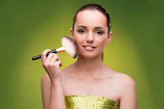 La belle femme appliquant le maquillage dans le concept de beauté Image libre de droits