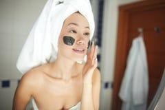 La belle femme appliquant le nettoyage de visage frottent photos stock