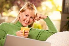 La belle femme apprécie sa boisson et ordinateur portatif chauds Photo stock