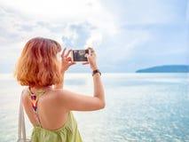 La belle femme asiatique avec les cheveux courts utilisant le téléphone intelligent adoptent une position de paysage marin de pho photographie stock