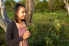 La belle femme asiatique est souriante et tenante un groupe de fleurs sauvages minuscules dans sa main Photographie stock libre de droits