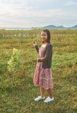 La belle femme asiatique est souriante et tenante un groupe de fleurs sauvages minuscules dans sa main Image stock