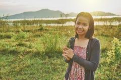 La belle femme asiatique est souriante et tenante un groupe de fleurs sauvages minuscules dans sa main Images stock