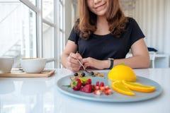 La belle femme asiatique a eu plaisir à manger le gâteau orange avec le fruit mélangé par la cuillère en café image stock