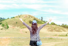 La belle femme asiatique heureuse avec le chapeau et le sac a tendu ses bras prêts à commencer des vacances avec la montagne de p images libres de droits