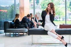 La belle femme attirante d'affaires regarde l'appareil-photo et le hav photo stock