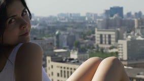 La belle femme attirante regarde in camera souriante, la ville blanche de robe de belles jambes banque de vidéos
