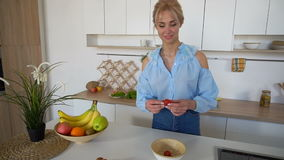 La belle femme au foyer féminine prépare le petit déjeuner sain avec le sourire et se tient à la table dans la cuisine lumineuse  banque de vidéos
