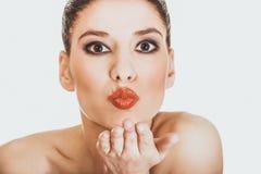 La belle femme avec composent souffler un baiser Photographie stock