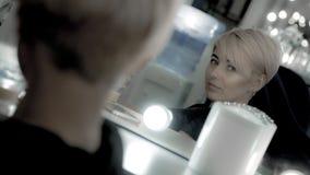La belle femme avec la coupe de cheveux courte et la perforation faciale regardent le miroir elle-même photographie stock libre de droits
