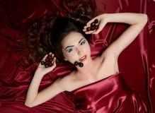 La belle femme avec de longs cheveux dans une soie rouge Images stock
