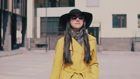 La belle femme avec de longs cheveux foncés en manteau jaune et verres vient avec le bagage clips vidéos