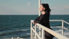 La belle femme avec de longs cheveux noirs se tient sur le pilier et enjoing la vue impressionnante sur la mer après séance d'ent banque de vidéos