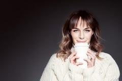 La belle femme avec de longs cheveux portant les prises rouges de chapeau et de chandail montre la tasse de café jetable de papie photos stock