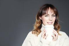 La belle femme avec de longs cheveux portant les prises rouges de chapeau et de chandail montre la tasse de café jetable de papie images libres de droits