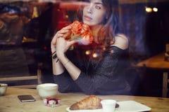 La belle femme avec de longs cheveux tenant les roses rouges fleurit à disposition Photos stock