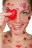 La belle femme avec des baisers sur le visage tenant le coeur observe Photographie stock libre de droits