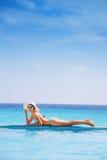 La belle femme avec des lunettes de soleil s'étend sur la côte Image stock