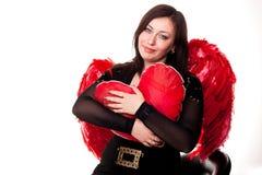 La belle femme avec le coeur rouge dans l'ange rouge s'envole Photos libres de droits