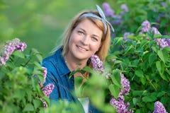 La belle femme avec le groupe lilas et la guirlande des fleurs font du jardinage au printemps, portrait de jeune mère enceinte Image stock