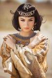 La belle femme avec le maquillage de mode et la coiffure aiment la Reine égyptienne Cléopâtre dehors contre le temps venteux de d Image libre de droits