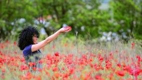 La belle femme avec le pavot fleurit au printemps banque de vidéos