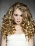La belle femme avec les cheveux bouclés et composent images stock