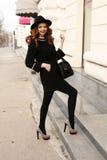 La belle femme avec les cheveux bouclés foncés et le sourire avec du charme, porte les vêtements élégants Photographie stock