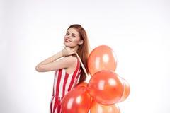 La belle femme avec les cheveux rouges sur le fond d'isolement par blanc tient un groupe de ballons Photographie stock libre de droits