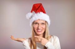 La belle femme avec un chapeau de Santa fait des gestes la paume  Photographie stock