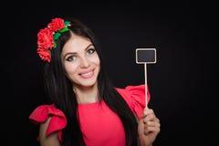 La belle femme avec une guirlande des fleurs rouges tient une plaque en bois Image stock