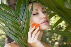 La belle femme ayant le masque facial de papaye fraîche s'appliquent PAP frais Photos libres de droits