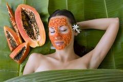 La belle femme ayant le masque facial de papaye fraîche s'appliquent PAP frais Photos stock