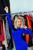 La belle femme blonde d'amusement choisit des vêtements dans la boutique image stock