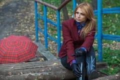 La belle femme blonde dans la veste en tweed et les gants en cuir repose o Photos stock
