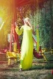 La belle femme blonde de mode dans la longue robe jaune élégante se tiennent prêt le carrousel de vol en été de sandales de talon photographie stock