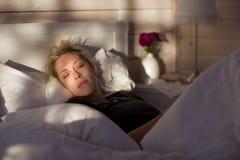 La belle femme blonde dort dans le lit, dans la maison en bois photographie stock