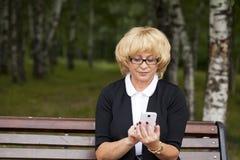 La belle femme blonde mûre invite un téléphone portable Photo stock