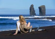 La belle femme blonde s'assied à une plage noire de sable avec des messages dans des bouteilles, regardant la mer Formations de r photo stock