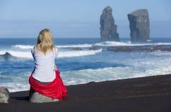 La belle femme blonde s'assied sur la pierre de plage, près aux formations de roche sauvages iconiques à côté de Mosteiros, en îl image libre de droits