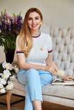 La belle femme blonde sexy s'assied sur le sofa dans les toilettes de toilettes Photo libre de droits