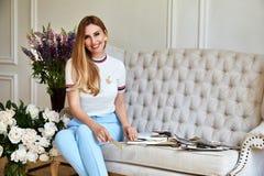 La belle femme blonde sexy s'assied sur le sofa dans les toilettes de toilettes Photos libres de droits